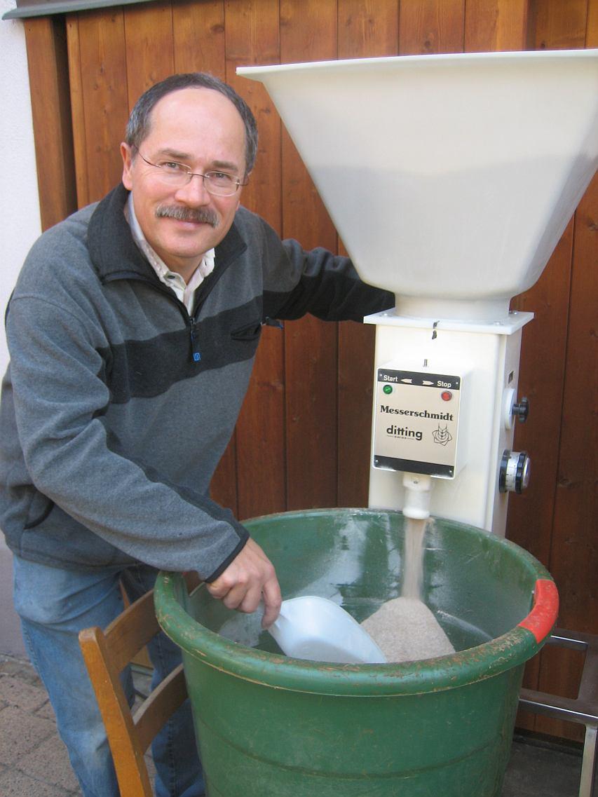 Walter Fitzke mahlt Malz mit der Getreidemühle